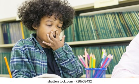 african boy is sitting and learning have stuffy nose