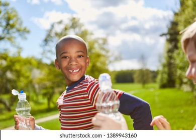 African boy smiles naughty and drinks water from a water bottle in the park