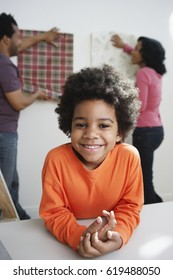 African boy smiling while parents choose wallpaper