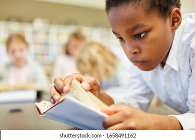 African boy as a student reads concentrated in a book in the library