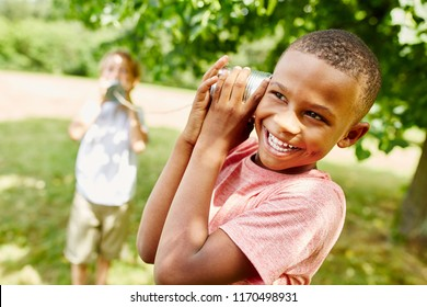 African boy with tin can telephone playing with friend