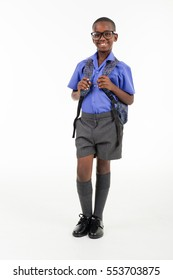 African boy wearing his school uniform and a rucksack ready to go back to school.