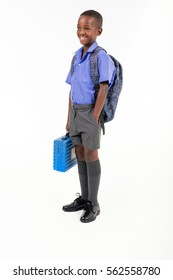 African boy wearing his school uniform and holding a school bag ready to go back to school.