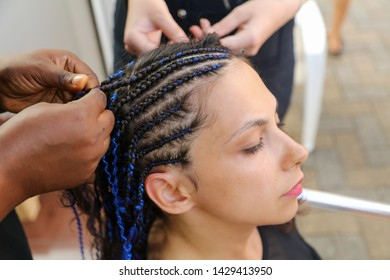 African braids are braided on head in salon .