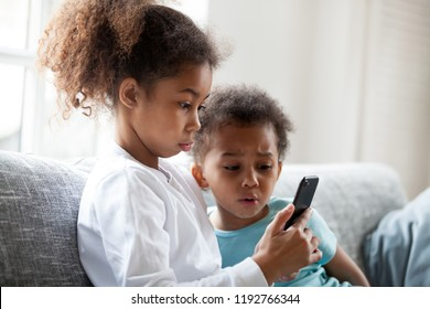African brother and sister sitting on couch at home using mobile phone.Close up surprised daughter and frustrated son looking at device screen. Technology new generation addicted with gadgets concept