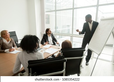 African business coach gives presentation at board meeting working with flipchart, executive team sit at conference table listening to black speaker presenting new marketing sales project in office