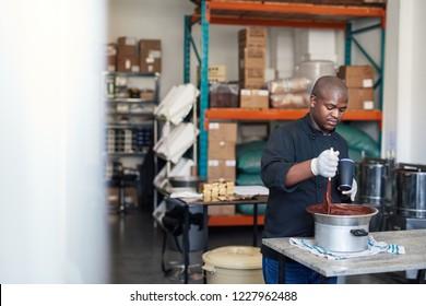 African business owner in an artisanal chocolate making factory using a hair dryer to keep chocolate melted in a bowl