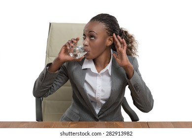 African business woman sitting at her desk and drinking water isolated on white background