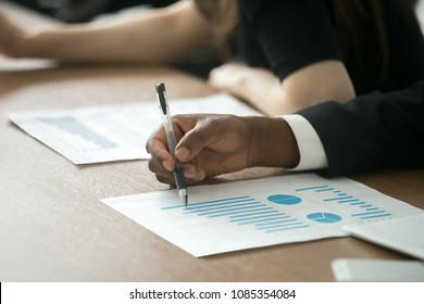 African businessman, business investor or customer analyzing benefits in project statistics document with rising increasing graphs, checking financial result in report paper at meeting, close up view