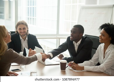 African businessman and caucasian businesswoman shaking hands over conference table at multiracial meeting, black man entrepreneur handshaking white woman welcoming new partner and expressing respect