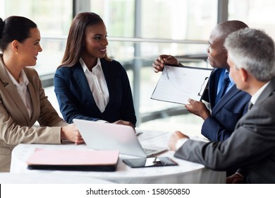 african businessman explaining sales graph to colleagues in meeting