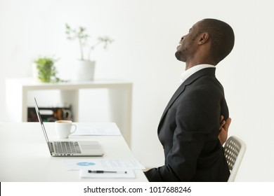 African businessman feels strong backache sitting on uncomfortable office chair at work, black man in suit suffering from ache pain in tensed back muscles after sedentary work in incorrect posture