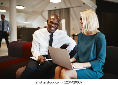 African businessman laughing with a coworker while sitting together on a sofa in a modern office working online with a laptop