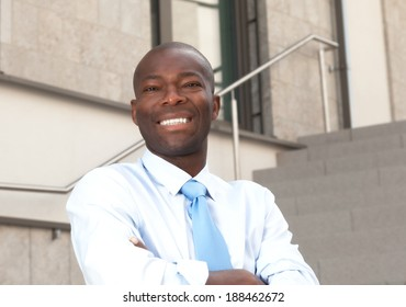 African businessman on stairs laughing at camera