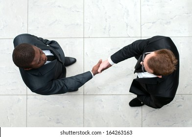 African businessman shaking hands with a caucasian one. view from above