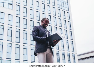African businessman standing with a Notepad on the background of a skyscraper with a panoramic glass