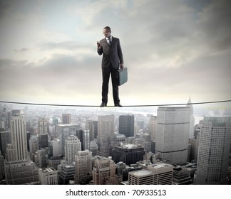 African businessman standing on a cable over a cityscape and using a mobile phone