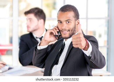 African businessman talking on his mobile phone and showing thumb up. Three successful business people sitting in the office and do business while businessman working at his desk