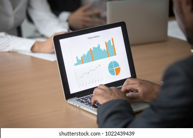 African businessman working on computer analyzing project statistics planning corporate strategy at meeting, black employee using laptop with digital business data stats on screen, close up rear view
