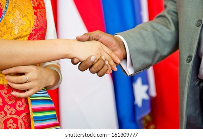 African businessman's hand shaking white Chinese woman's hand.
