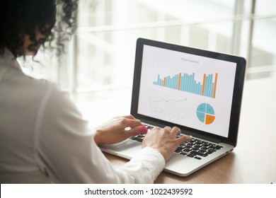 African businesswoman analyzing statistics on laptop screen, working with financial graphs charts online, using business software for data analysis and project management concept, rear close up view