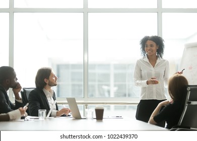 African businesswoman giving presentation working with flipchart in meeting room making business offer to partners, black woman reporting about work result on whiteboard, explaining new project idea