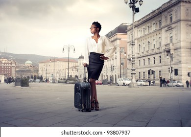 African businesswoman holding a trolley case on a city square