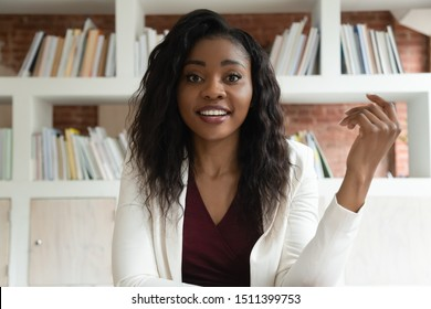 African businesswoman sit indoors looks at camera talking with corporate client discuss common business use virtual communication make video call, skilled coach helps to apprentice distantly concept
