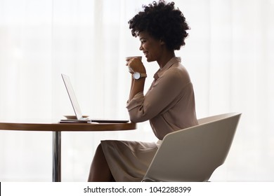 African businesswoman smiling while using laptop and drinking coffee in office. Side view of office worker having coffee while working on laptop.