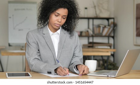 African Businesswoman Writing Letter at work