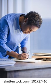 African businesswoman writing on paperwork