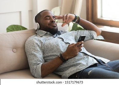 African calm guy hold smart phone fell asleep lying on couch listens music on headphones enjoy song or meditation audio course feels serenity inner harmony and balance, no stress mood, leisure concept