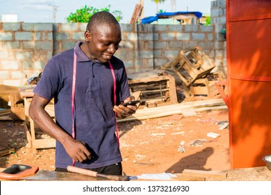 african carpenter smiling while checking his phone in his workshop