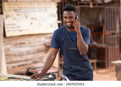 african carpenter smiling while making a phone call