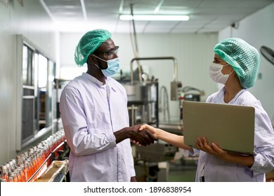 African and Caucasian Lab Specialist shake hand for cooperation in quality assurance of production in beverage industry with labtop check list