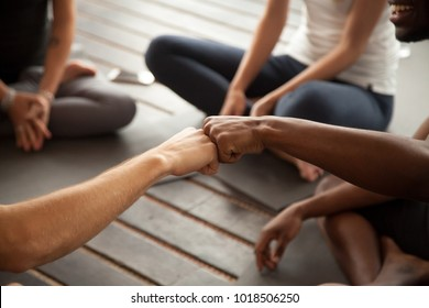 African and caucasian men fist bumping at group meeting in gym studio, two multiracial black and white friends greeting with friendly gesture celebrating team training teamwork, hands close up view