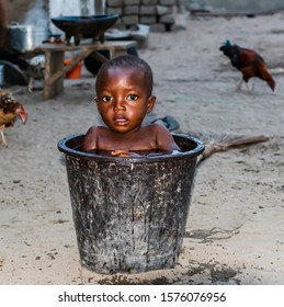 African child bathing in a bucket of water to cool off a warm evening in the fishing village of Ada Foah Ghana West Africa.