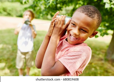 African child calling friend with tin can telephone