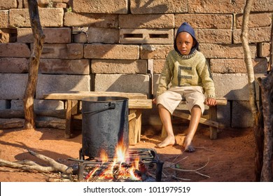 African child cooking outdoors, watching supper, kitchen in the village, Botswana
