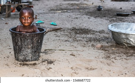 African child cools down in a bucket of water during a hot afternoon. Photo from a fishing village Ada Foah Ghana West Africa.