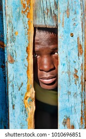 African child hiding behind a door in the village, Botswana