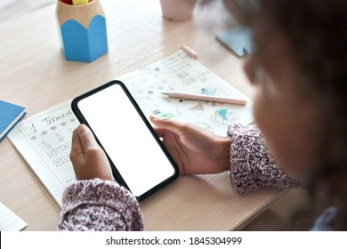 African child kid girl holding phone distance learning class using mobile tech, watching online tutoring video lesson in app studying at home school classroom, over shoulder mock up screen ads view.