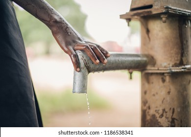 African child places hand on spout of water fountain pump preparing to carry water.