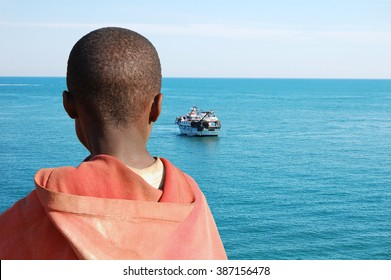 An African child as she watches a barge with his friends on board