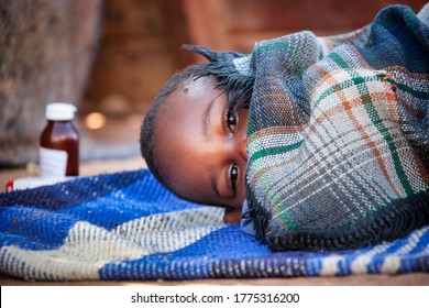 african child toddler sick with malaria medicine in the background, laying down on a blanket in the yard