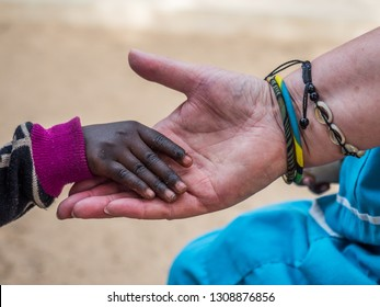 African child is touching hand of white woman. Diversity concept. Senegal. Africa.