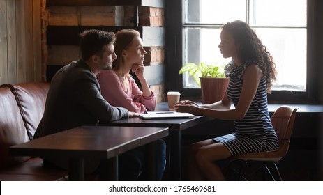 African company representative sell services to clients, wedding planner discuss with bride groom moments of future event at meeting in cafe, spouses listen realtor give advice make real estate offer