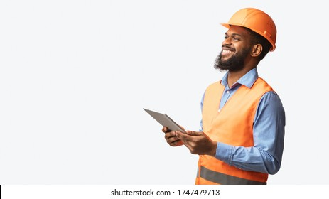 African Construction Foreman Worker Holding Tablet Computer, Smiling Looking Aside Over White Studio Background. Empty Space, Panorama