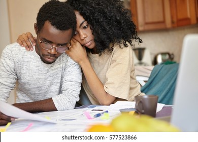 African couple is bankrupt. Sad male in glasses holding piece of paper feeling effortless to do something to save his business while his strong wife hugging him tenderly, trying to cheer him up