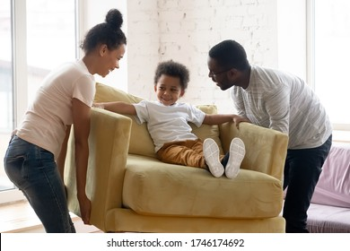 African couple carrying armchair where sit adorable small toddler son. Happy family placing delivered furniture bought in modern store, furniture shop advertisement, relocation day at new home concept